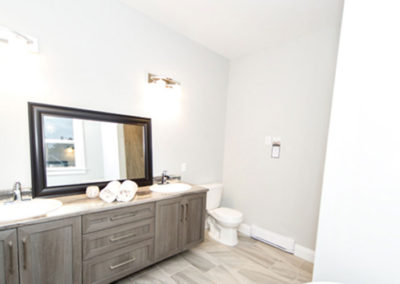 Bungalow has a large secondary bathroom with double sinks and rustic cabinets
