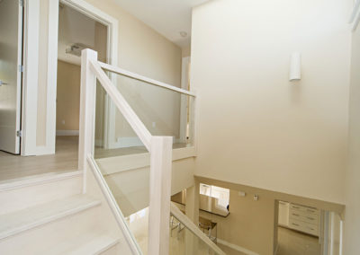 bright staircase with skylight and glass railings created by custom house builders